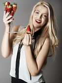 stock photo of strawberry blonde  - Pretty blonde girl holding glass of Strawberries - JPG