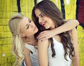 stock photo of adoration  - Two happy beautiful teen girls having fun outdoor against colored wall - JPG