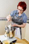 picture of food processor  - Woman pour sugar and spices into food processor when baking - JPG