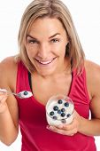 foto of yogurt  - Portrait of Woman enjoying eating her yogurt and blueberries isolated on white background - JPG