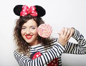 foto of lolita  - young happy curly woman with mouse ears holding lollipop - JPG