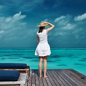 stock photo of jetties  - Woman on a tropical beach jetty at Maldives - JPG