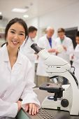stock photo of microscopes  - Young medical student working with microscope at the university - JPG
