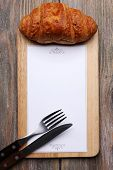 image of croissant  - Cutting board with menu sheet of paper and croissant on rustic wooden planks background - JPG