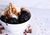 foto of doilies  - Dessert with prunes and nuts in cup on lace doily on color wooden background - JPG