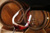 stock photo of merlot  - Pouring red wine from bottle into glass with wooden wine casks on background - JPG