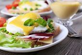 foto of benediction  - Toast with egg Benedict and tomato on plate on wooden table - JPG