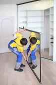 foto of premises  - Young worker raises mirrored door on corner closet in room  - JPG