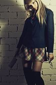 image of lolita  - Schoolgirl with cutter posing over brick wall - JPG