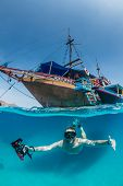 image of life-boat  - Snorkeller dives under a traditional wooden boat in clear tropical waters - JPG