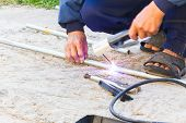 stock photo of welding  - Worker welding the steel part by manual without safety danger concept - JPG