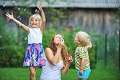 foto of blowers  - mother and her children play with bubble blower on green lawn - JPG