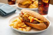 image of cheesesteak  - cheesesteak sandwich accompanied by fries and an ice cold cola - JPG