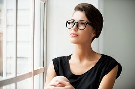 stock photo of short legs  - Beautiful young short hair woman sitting on window sill and looking away - JPG