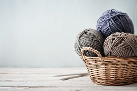 stock photo of coil  - Wool yarn in coils with knitting needles in wicker basket on light blue background - JPG