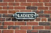 picture of old lady  - Old antique ladies restroom sign on red brick wall - JPG