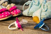 foto of pacifier  - Baby shoes and pacifiers pink and blue on the old wooden background - JPG
