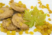 stock photo of baked raisin cookies  - Integral cookies and yellow raisins with a large green flower on white - JPG