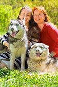 picture of girlie  - laughing mother and daughter along with two dogs in park on background of green trees - JPG