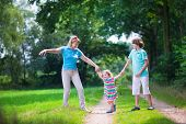 stock photo of children walking  - Happy active woman enjoying hiking with two children school age boy and cute curly toddler girl walking together in a beautiful pine wood forest on a sunny summer day - JPG