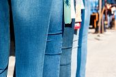 stock photo of mannequin  - Row of mannequins with different coloured jeans on market - JPG