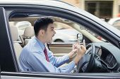 picture of scream  - Young businessman driving a car and looks angry showing two middle fingers and screaming - JPG