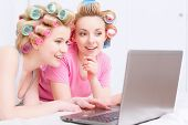 picture of pajamas  - Young beautiful girls wearing pajamas and colorful hair rollers lying on the bed and looking interestedly at laptop at home party in the light room - JPG