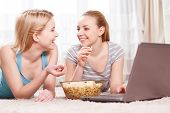 stock photo of pajamas  - Pajama party. Two young beautiful blond girls wearing pajamas lying on the floor eating popcorn and looking at each other near the laptop