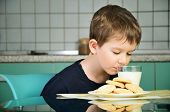 stock photo of milk  - cheerful little boy sniffs with pleasure milk sitting at the dinner table - JPG