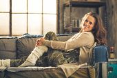 stock photo of legs apart  - An elegant brunette smiling woman in comfortable casual clothing leggings and a cardigan is relaxing on a loft sofa - JPG