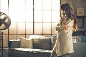 picture of comfort  - A brunette woman in comfortable clothing is standing in a loft living room holding her phone arms crossed looking away - JPG
