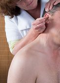 image of pointed ears  - Woman acupuncturist prepares to tap needle around ears of man - JPG