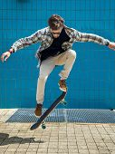 stock photo of skateboard  - Skateboarder jumping in city on skateboard at the background wall tiles - JPG