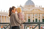 picture of eskimos  - In profile a mother and daughter give each other Eskimo kisses in Vatican City in Rome Italy - JPG
