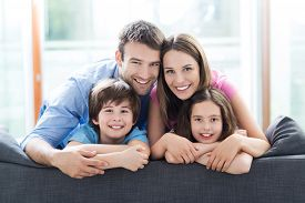 picture of four  - Family relaxing on sofa - JPG