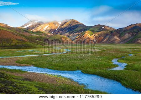 Snow lies in the hollows of colorful rhyolite mountains. Green Valley is flooded with melt water.  E