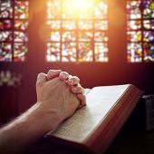 Hands folded in prayer on a Holy Bible in church concept for faith, spirituality and religion poster