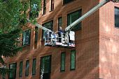 picture of cherry-picker  - workers in cherry picker inspecting window of brick building - JPG