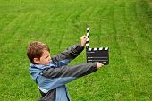 boy in jacket with cinema clapper board in their hands