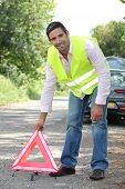 Man in fluorescent vest putting out a warning triangle by a breakdown