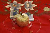 stock photo of x-max  - Small golden apple on red decorative table - JPG