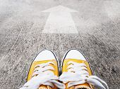 Selfie Feet Wearing Yellow Sneakers In Front Of Arrow On Concrete Road. Start Moving Forward Concept poster