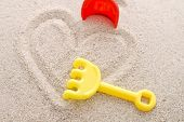 picture of playmates  - Heart shape drawn on sand with yellow toy rake - JPG