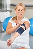 Senior woman with bandage on elbow in fitness center