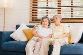 Asian Elderly Couple Watching Television In Living Room At Home, Sweet Couple Enjoy Love Moment Whil poster