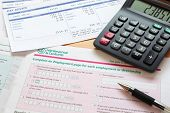 Photo of a UK self assessment tax return with calculator and payslips. The payslip is a mock up the