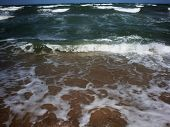 Frothy Waves Of The Sea On The Sandy Beach. Foamy Wave Rolls poster