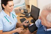 stock photo of hypertensive  - British nurse taking senior man - JPG