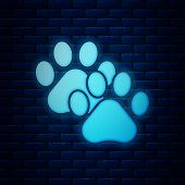 Glowing Neon Paw Print Icon Isolated On Brick Wall Background. Dog Or Cat Paw Print. Animal Track. V poster