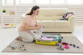 Holidays, Voyage And Travel Concept - Young Woman Collects A Suitcase At Home In The Bedroom, A Lot  poster